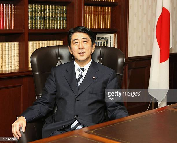 Newly elected Japanese ruling Liberal Democratic Party President Shinzo Abe smiles as he settles into the presidential seat at the LDP headquarters...