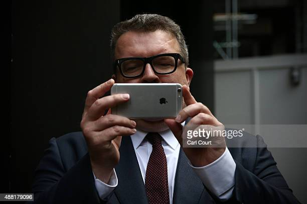 Newly elected Labour Party deputy leader Tom Watson takes a photograph of press photographers as he leaves the Labour Party headquarters on September...