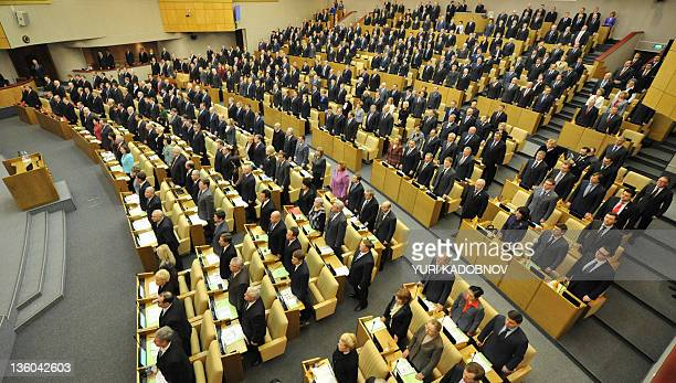 Newly elected lawmakers listen to the national anthem during the opening of the first session of Russia's lower house of parliament the State Duma in...