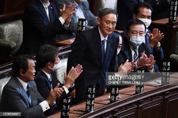 Newly elected leader of Japan's Liberal Democratic Party Yoshihide Suga is applauded by Deputy Prime Minister and Finance Minister Taro Aso , Foreign...