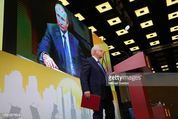 Newly elected leaders of the united A Just Russia-For Thuth Party Sergei Mironov speeches as President Vladimir Putin is seen on the screen during an...
