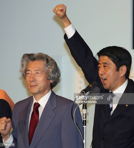Newly elected Liberal Democratic Party President Shinzo Abe and Prime Minister Junichiro Koizumi raise their arms during the presidential election at...