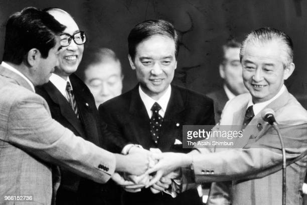 Newly elected Liberal Democratic Party president Toshiki Kaifu shakes hands with outgoing Prime Minister Sosuke Uno defeated candidates Shintaro...