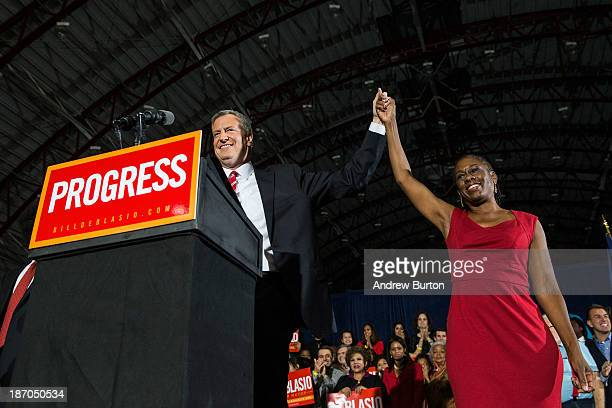 Newly elected New York City Mayor Bill de Blasio holds hands with his wife Chirlane McCray at his election night party on November 5 2013 in New York...