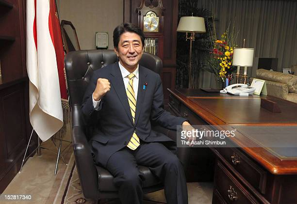 Newly elected opposition Liberal Democratic Party President Shinzo Abe poses for photograghs in the LDP Presidential seat at the LDP headquarters on...