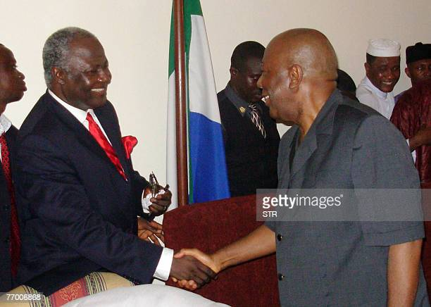 Newly elected president Ernest Bai Koroma shakes hands with outgoing leader Ahmad Tejan Kabbah 17 September 2007 in Freetown after winning a tense...