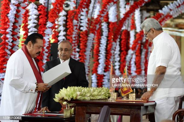 Newly elected Prime Minister Mahinda Rajapakse takes the oath of the office as Minister of finance, culture and housing in front of his brother, Sri...