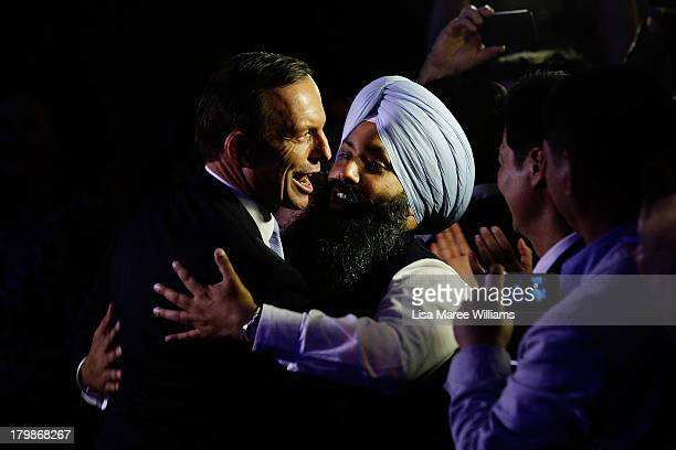 Newly elected Prime Minister Tony Abbott is hugged by a Liberal Party member as he arrives to deliver his victory speech on September 7 2013 in...