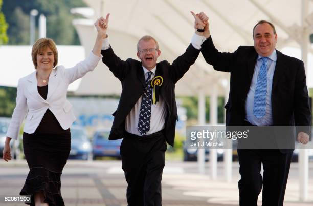 Newly elected Scottish National Party MP for the Glasgow east constituency John Mason walks with his deputy leader Nicola Sturgeon and leader Alex...