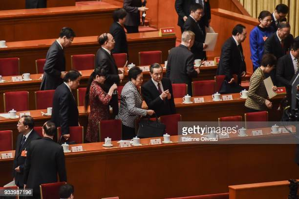Newly elected State councilors Wang Yi talks with another official after the seventh plenary session of the 13th National People's Congress at the...