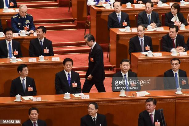 Newly elected State councilors Wang Yi walks by Chinese Premier Li Keqiang Chinese President Xi Jinping and Chairman of the NPC Li Zhanshu as he gets...