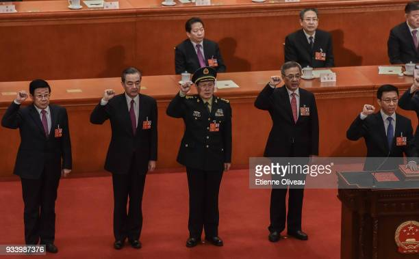 Newly elected state councilors Zhao Kezhi Wang Yi and Wei Fenghe Vice Premiers Hu Chunhua and Han Zheng swear an oath during the seventh plenary...