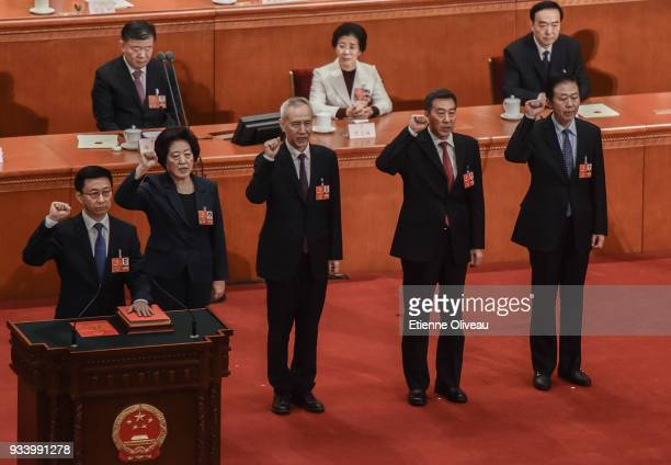Newly elected Vice Premiers Han Zheng Sun Chunlan and Liu He with State Councilors Wang Yong and Xiao Jie swear an oath during the seventh plenary...
