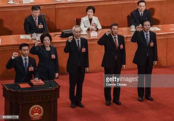 Newly elected Vice Premiers Han Zheng, Sun Chunlan and Liu He, with State Councilors Wang Yong and Xiao Jie swear an oath during the seventh plenary...