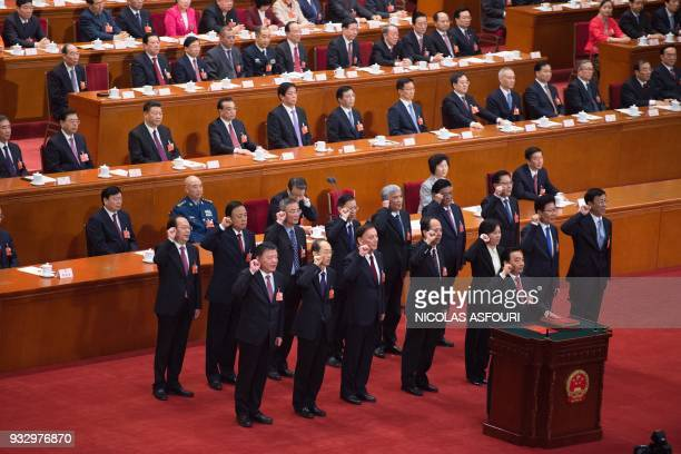 Newly elected vicechairmen of the National People's Congress led by Wang Chen swears an oath after being elected during the fifth plenary session of...