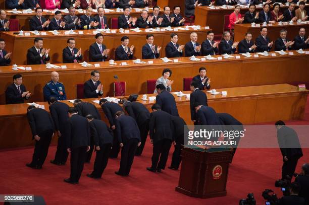 Newly elected vicechairmen of the National People's Congress led by Wang Chen bow after swearing an oath after being elected during the fifth plenary...