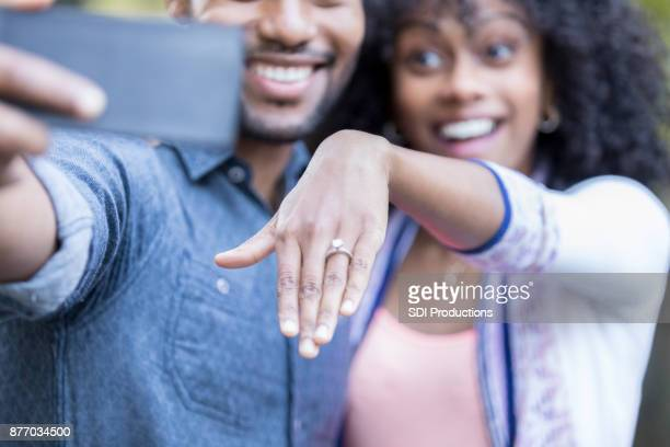 newly engaged couple show off engagement ring - black women engagement rings stock pictures, royalty-free photos & images