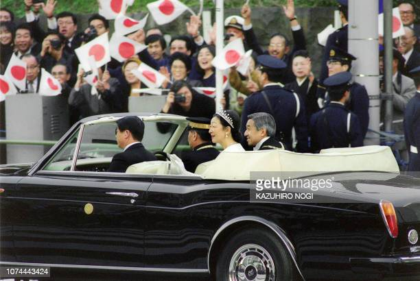 A newly enthroned Japanese Emperor Akihito and wife Empress Michiko proceed through central Tokyo in a motorcade acknowledging wellwishers 12...