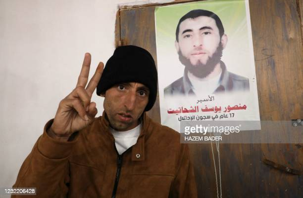 Newly free Palestinian prisoner Mansur al-Shahatit poses next to a poster of him following his release from a 17-years jail sentence at an Israeli...