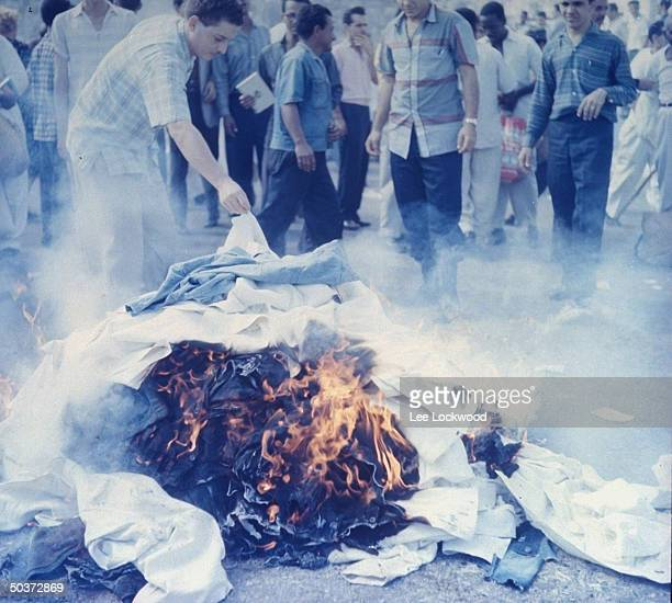 Newly freed political prisoners in Havana burning their uniforms in joyous celebration as Castro and victorious rebels head into city