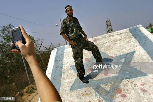 A newly graduated Palestinian security force officer poses for a photo as he stands on painted Israeli flag following a graduation ceremony of...