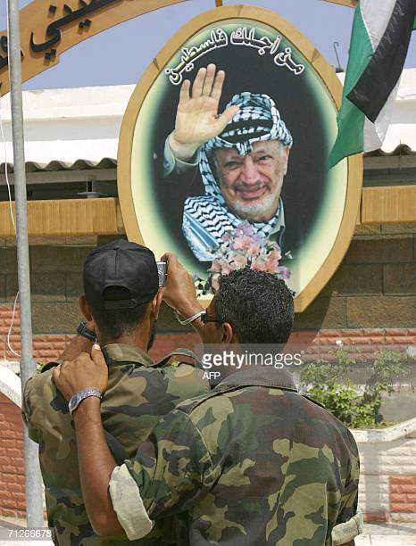 Newly graduated Palestinian security force officers take a souvenir snapshot of a portrait of late Palestinian leader Yasser Arafat following a...