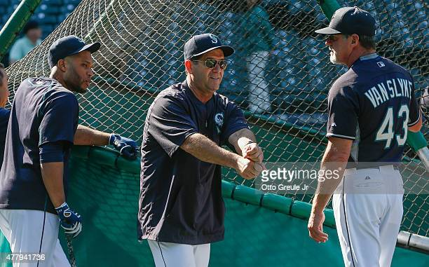 Newly hired hitting coach Edgar Martinez of the Seattle Mariners talks with outfield coach Andy Van Slyke as Robinson Cano listens in prior to the...