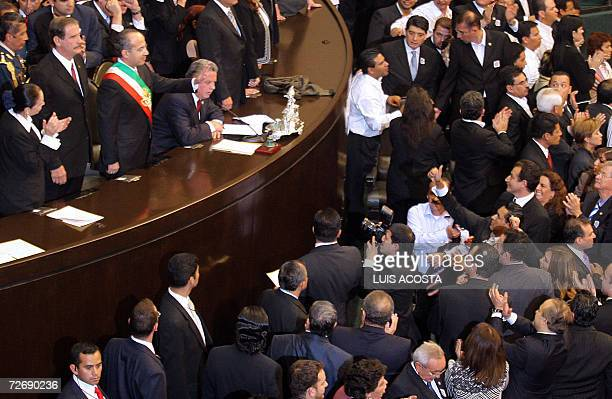 Newly inaugurated Mexican President Felipe Calderon waves to supporters next to outgoing Vicente Fox after taking the constitutional oath 01 December...
