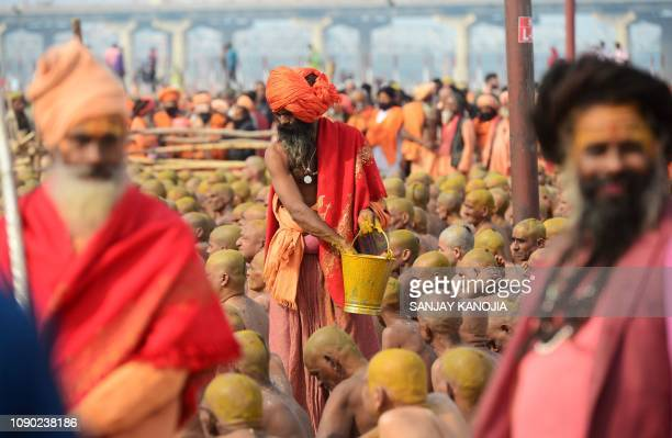 Newly initiated 'Naga Sadhus' sit as they perform rituals on the banks of the Ganges River during the Kumbh mela festival in Allahabad on January 27...