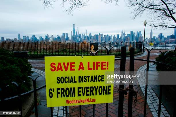 Newly installed sign encouraging social distancing to stop the spread of coronavirus is displayed on a closed park as the skyline of Manhattan is...