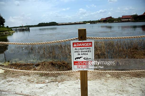 Newly installed signs warn of alligators and snakes on a closed section of beach following the death of a 2-year-old boy who was killed by an...
