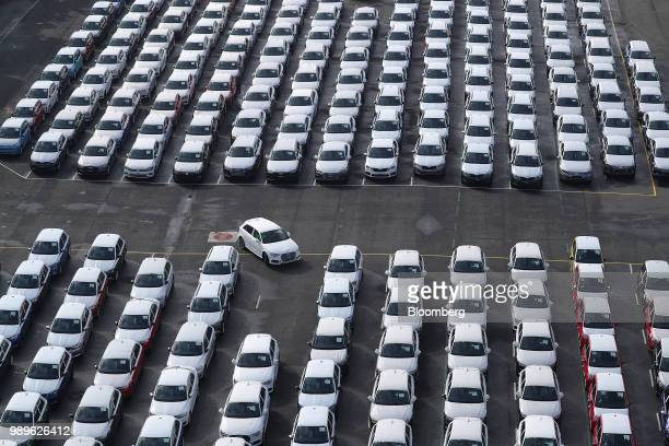 A newly manufactured Audi AG automobile is driven into a parking space as Volkswagen AG brand vehicles stand ahead of shipping outside the VW factory...