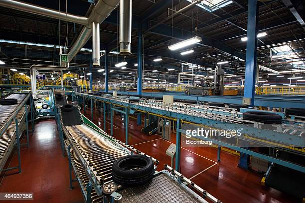Newly manufactured Hankook Tire Co automobile tires move along conveyors at the company's manufacturing plant in Geumsan South Korea on Monday March...
