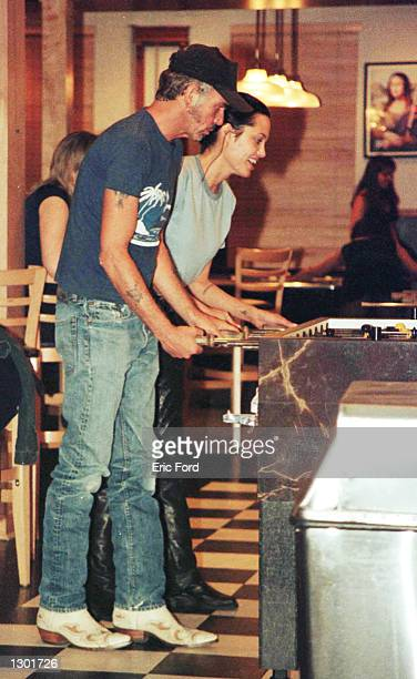 Newly married Billy Bob Thornton and Angelina Jolie play pinball at Jerry''s Famous Deli June 3 2000 in Studio City CA