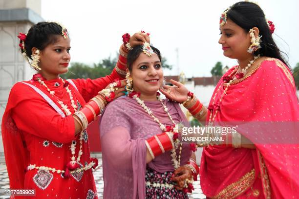 Newly married bride adorned with flowers poses on the occasion of the Teej festival during the Sawan month at the Durgiana Temple in Amritsar on July...