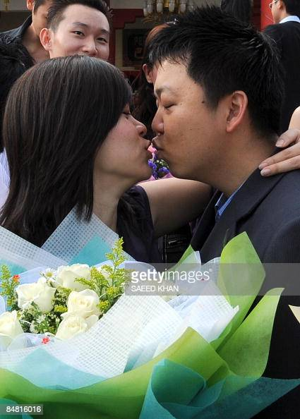 A newly married couple kisses after a mass-wedding ceremony