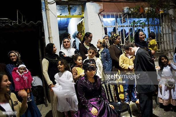 Newly married couple pose together with the guests of the wedding party for the photographer in front of the house in the district Tarlabasi on May...