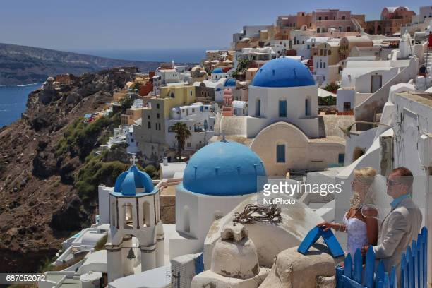 Newly married couple poses for wedding photos while on honeymoon in the village of Oia on Santorini Island Greece Santorini Island is without a doubt...