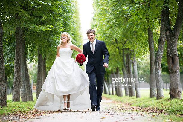 Newly married couple running in park