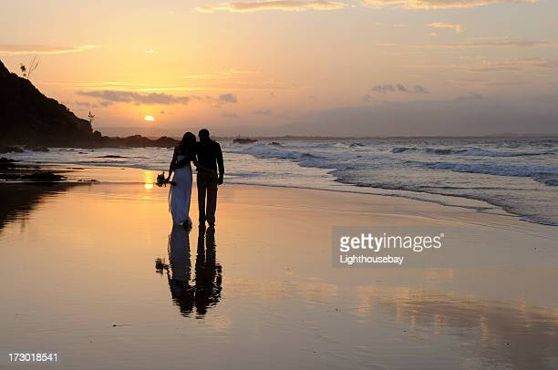Newly married couple walking away together on the beach