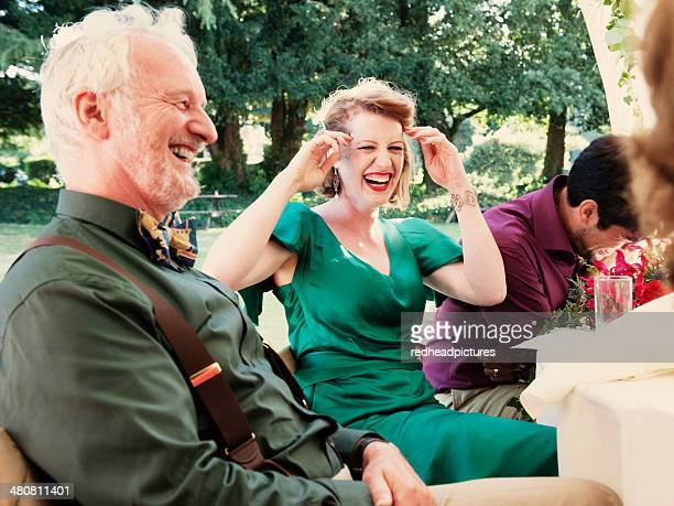 Newly married couple with parents laughing at wedding reception