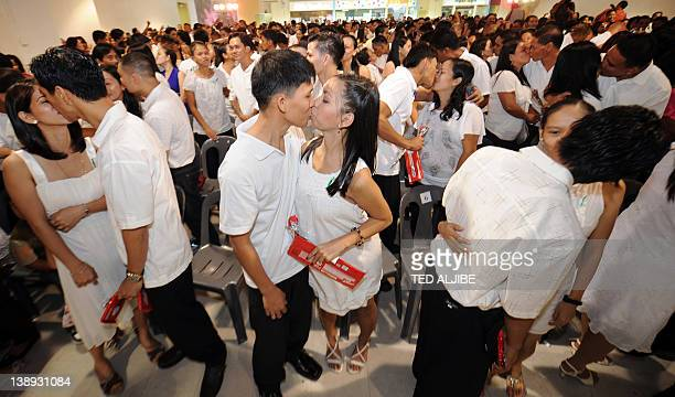 Newly married couples kiss during a mass wedding as part of Valentine's Day celebrations at a shopping mall in suburban Manila on February 14 2012...