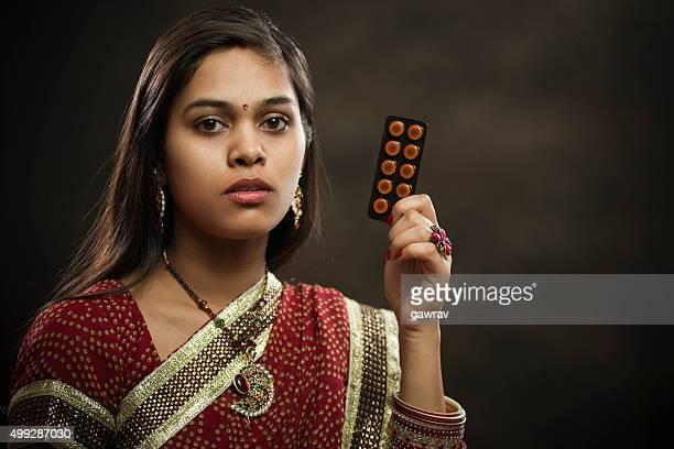 Frisch verheiratet Hindu junge Frau holding Päckchen der Medizin Tabletten.