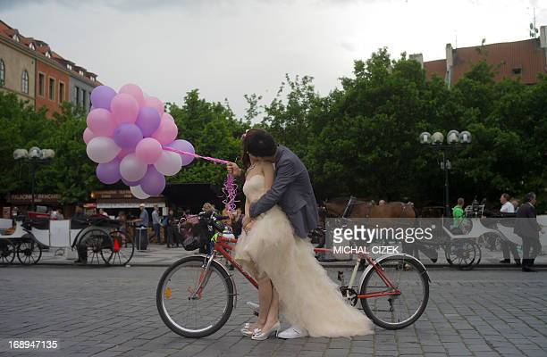 A newly married man from South Korea kisse his bride at the Old Town Square on May 17 2013 in Prague AFP PHOTO/MICHAL CIZEK