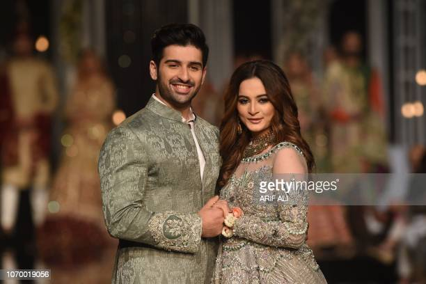 Newly married Pakistani actors Aiman Khan and Muneeb Butt present creations by designer Aosadya during the Pantene Hum Bridal Couture Week in Lahore...