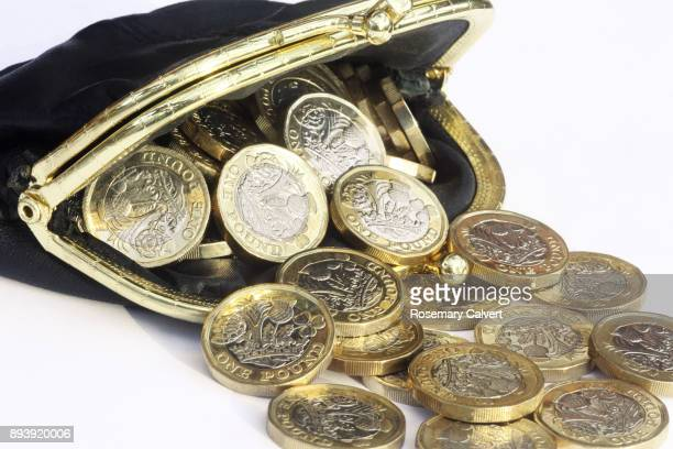 newly minted one pound coins spilling from leather purse. - clutch bag stock pictures, royalty-free photos & images