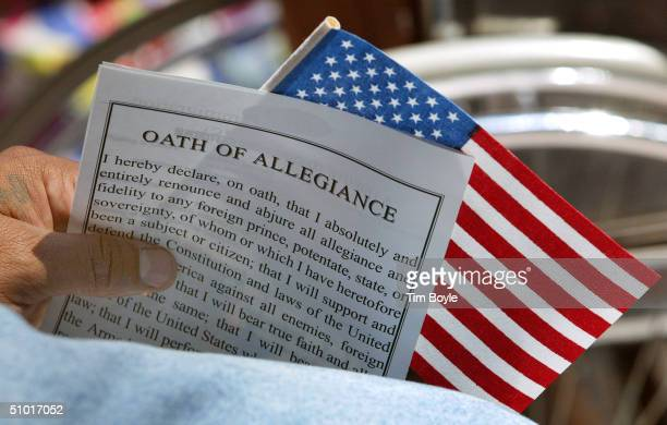"Newly naturalization U.S. Citizen holds an ""Oath Of Allegiance"" and a U.S. Flag during a naturalization ceremony July 1, 2004 in Chicago, Illinois...."