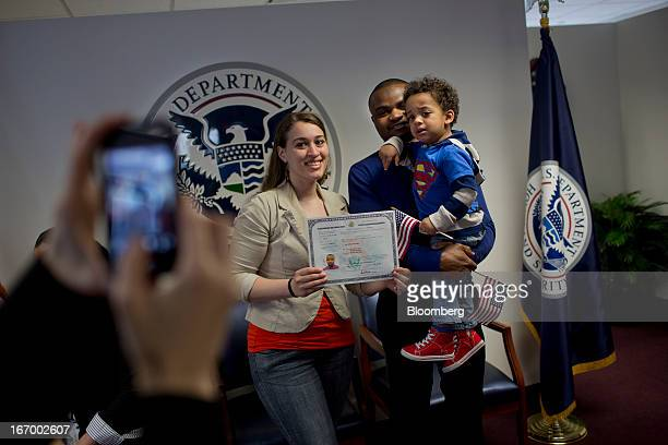 Newly naturalized American citizen Fayick Suleman from Ghana center stands for a photograph his wife Hanadi Suleman left and their son Laeyth Suleman...