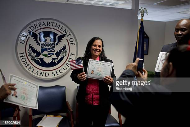 A newly naturalized American citizen takes a picture with her certificate of citizenship after a Naturalization Ceremony at the Jacob K Javits...