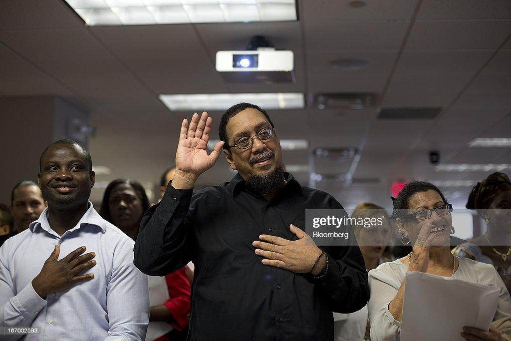 Newly naturalized American citizens recite the Pledge of Allegiance during a Naturalization Ceremony at the Jacob K. Javits Federal Building in New York, U.S., on Friday, April 19, 2013. A Senate plan to rewrite U.S. immigration law has stoked a years-old debate over allowing undocumented residents a chance to become citizens, a measure viewed by opponents as rewarding lawbreakers with 'amnesty' and undercutting American workers. Photographer: Victor J. Blue/Bloomberg via Getty Images